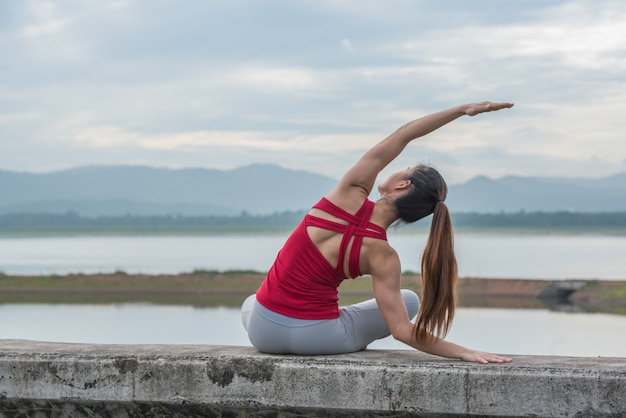 Mujer asiática en actitud de la yoga encima de la pared en el lago.