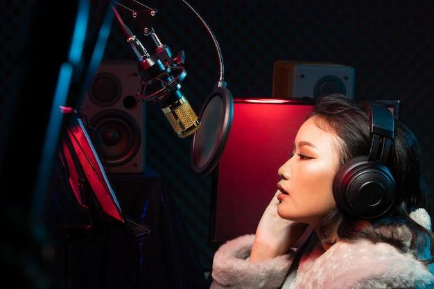La mujer asiática del adolescente canta la canción ruidosamente potencia el sonido