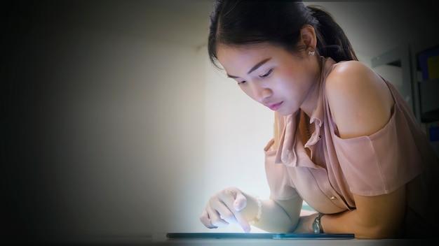 Mujer asiática adolescente lee y toca en un dispositivo de tableta en la oscuridad
