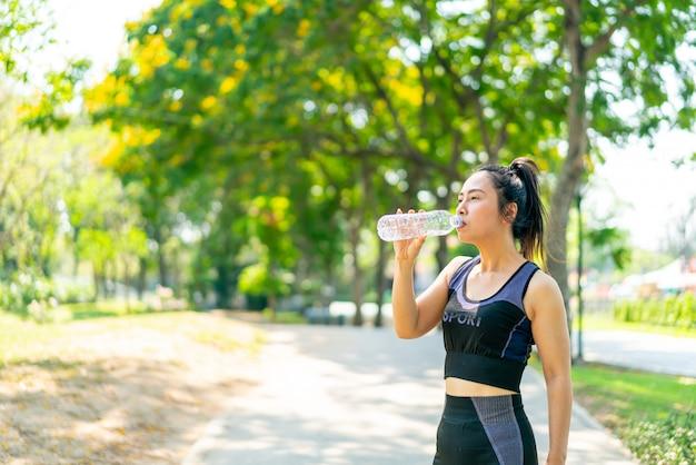 Mujer asiática agua potable en ropa deportiva