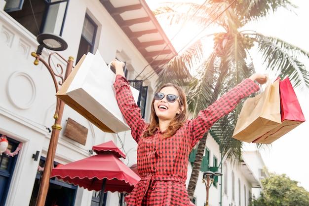 Mujer asiática alegre con algunos bolsos de compras