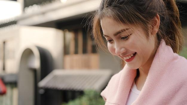 Mujer asiática alegre del blogger del backpacker que usa el smartphone para la dirección y que mira en mapa de ubicación mientras que viaja en chinatown en pekín, china.