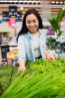 Mujer asiática alegre que escoge el verdor en colmado