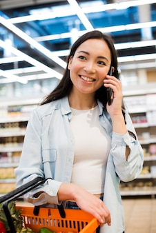 Mujer asiática alegre que lleva la cesta de compras y que habla en el teléfono móvil en colmado