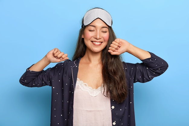 La mujer asiática alegre y relajada estira las manos después de despertar, se regocija de un buen día, disfruta de un sueño agradable, sonríe sinceramente, usa antifaz para dormir y pijama