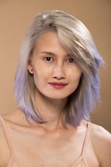 Mujer asiática antes de aplicar maquillaje estilo de pelo gris plateado. sin retoques, rostro fresco con labios, ojos, mejillas, piel suave y agradable. estudio de iluminación de fondo amarillo beige, para tratamiento de terapia estética