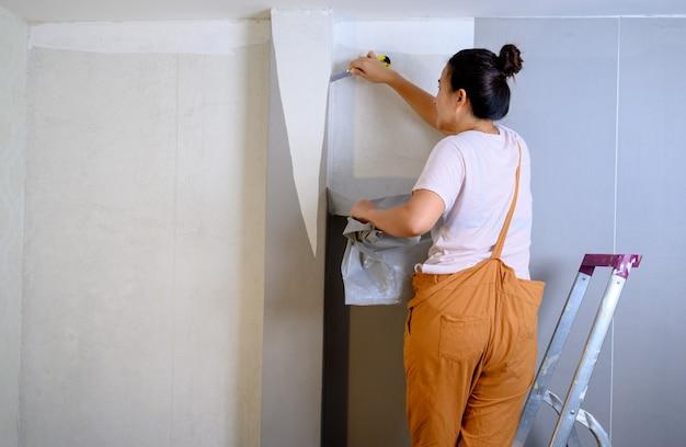 Mujer asiática aplicando nuevo papel tapiz en casa. renovar y decorar la casa.
