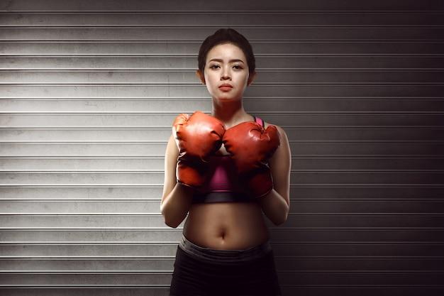 Mujer asiática de la aptitud con los guantes de boxeo rojos