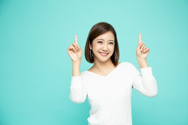 Mujer asiática apuntando al espacio vacío de la copia aislado