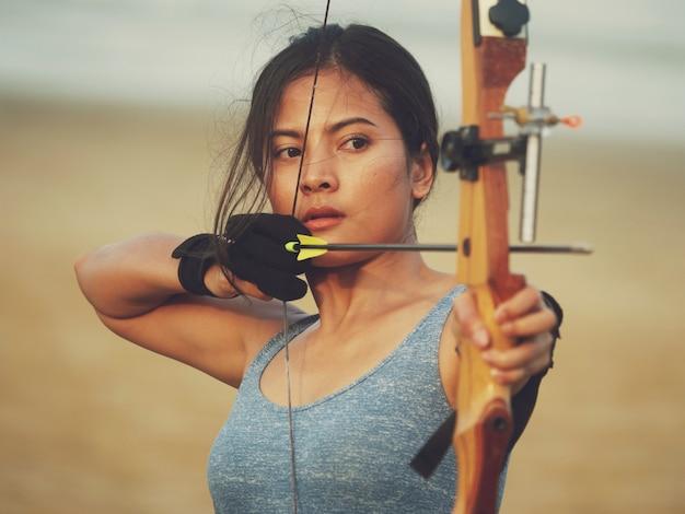 Mujer asiática con arco tiro con arco