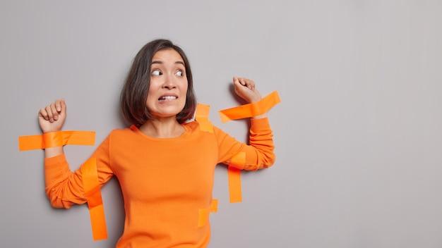 Mujer asiática asustada con cabello oscuro pegado con cintas adhesivas a la pared gris muerde los labios tiene expresión nerviosa aislada sobre la pared gris