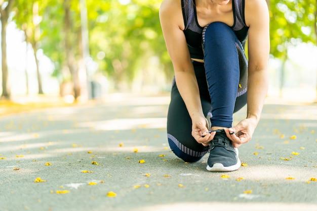 Mujer asiática atar cordones de los zapatos y prepararse para correr al aire libre