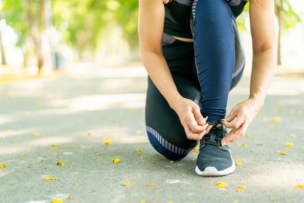 Mujer asiática atarse los cordones de los zapatos y preparándose para correr al aire libre