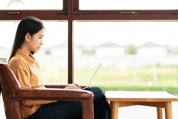 Mujer asiática atractiva joven que se sienta o que trabaja en el café