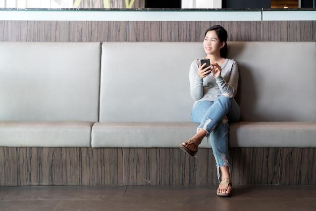 Mujer asiática atractiva joven que sienta la pierna cruzada en el sofá del sofá