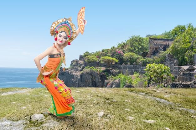 Mujer asiática bailando la danza tradicional balinesa (danza kembang girang) en el acantilado