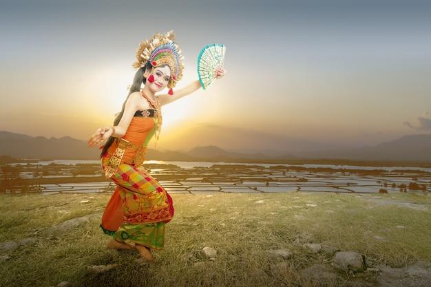 Mujer asiática bailando la danza tradicional balinesa (danza kembang girang) al aire libre