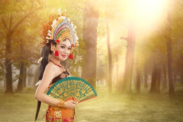 Mujer asiática bailando la danza tradicional balinesa (danza kembang girang) en el campo
