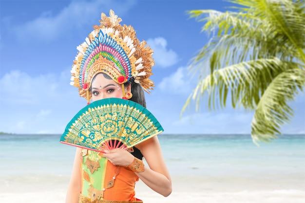 Mujer asiática bailando la danza tradicional balinesa (danza kembang girang) en la playa