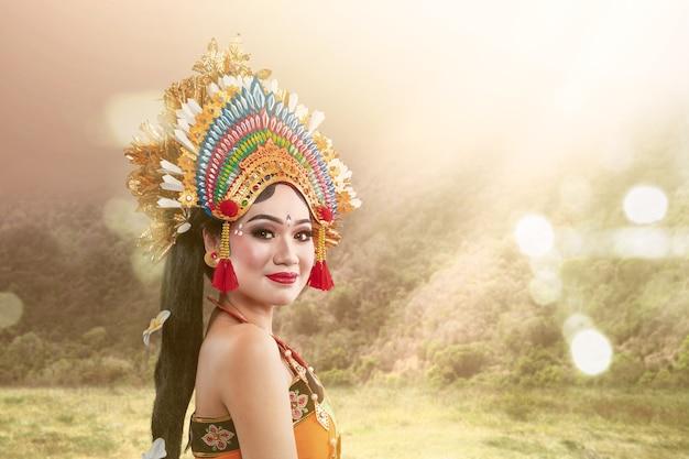 Mujer asiática bailando danza tradicional balinesa con luz solar