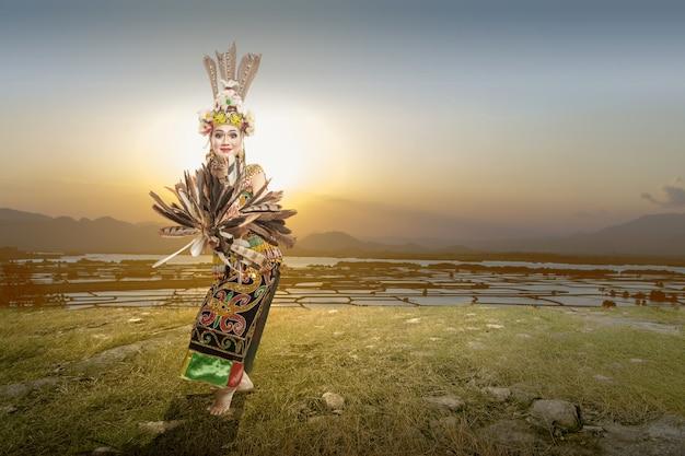 Mujer asiática bailando la danza tradicional de kalimantan oriental (danza giring-giring) al aire libre