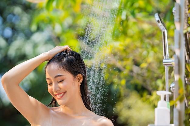 Mujer asiática bañándose al aire libre, se lavó el cabello en un estado de ánimo relajado.
