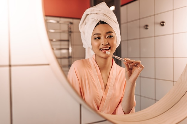 Mujer asiática en bata rosa y toalla blanca cepillándose los dientes
