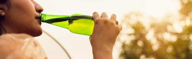 Mujer asiática beber agua de botella verde en la noche de vacaciones y relajarse tiempo.