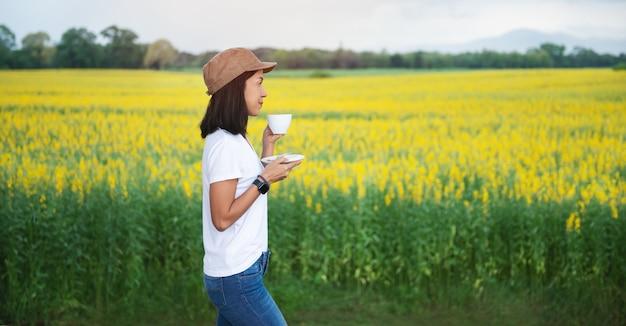 Mujer asiática beber café con taza en el campo con flores amarillas y montaña