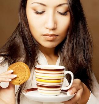 Mujer asiática bebiendo café o té