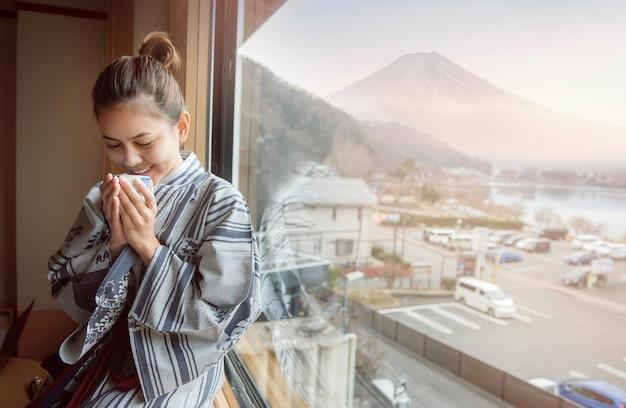 Mujer asiática está bebiendo té verde con la montaña fuji, estilo de japón