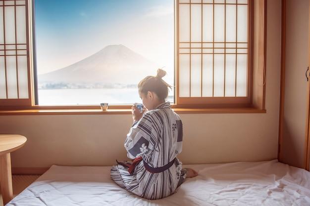 Mujer asiática está bebiendo té verde con la montaña fuji, estilo japón