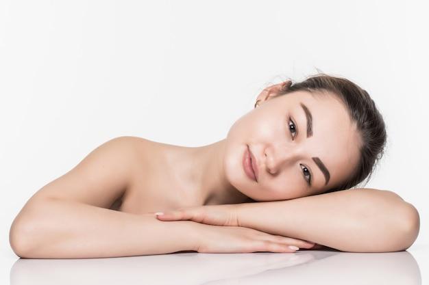 Mujer asiática de la belleza del cuidado de la piel de la cara hermosa que se acuesta con la reflexión de espejo aislada en la pared blanca.