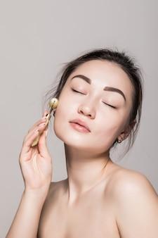 Mujer asiática de la belleza que relaja la cara que da masajes con el retrato de la belleza de la terapia de la tensión de la relajación facial del rodillo de la cara del jade en la pared blanca.
