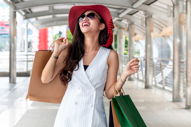 Mujer asiática de la belleza que sostiene el bolso de compras en la ciudad al aire libre.