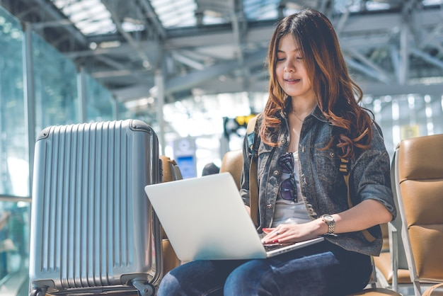 La mujer asiática de la belleza que usa el ordenador portátil con la maleta mientras que espera saca el vuelo