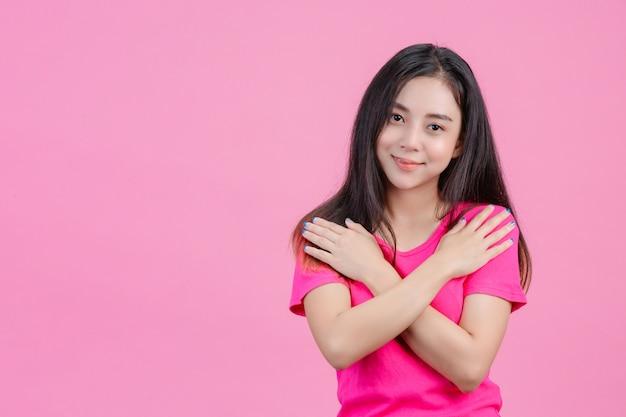 La mujer asiática blanca linda posa y se ama en un rosa.