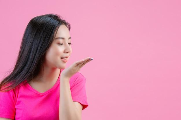 Mujer asiática blanca que sopla el polvo en su mano izquierda en un rosa.