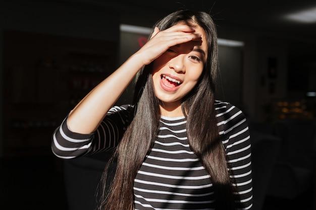 Mujer asiática con la boca abierta en la cafetería