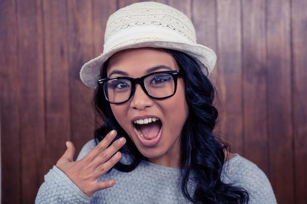 Mujer asiática con la boca abierta contra la pared de madera