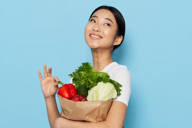 Mujer asiática con bolsa de papel con verduras