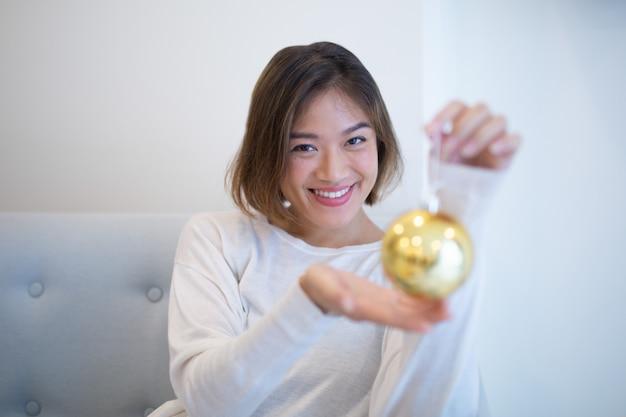 Mujer asiática bonita feliz con el pelo corto que sostiene la bola de oro