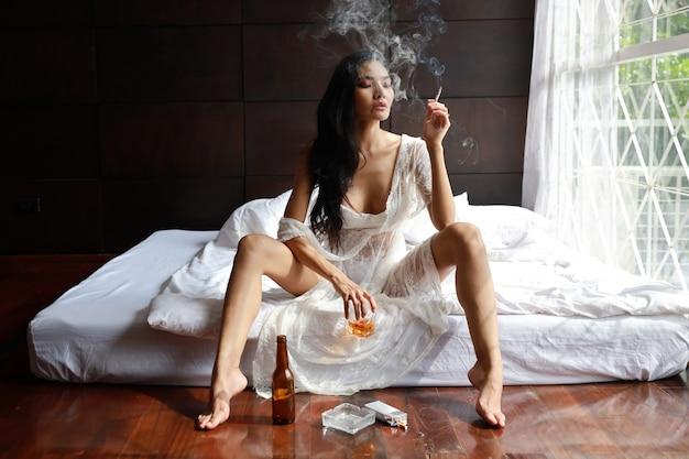 Mujer asiática borracha en lencería blanca, bebiendo y fumando mientras sostiene una botella de alcohol licor y sentado en la cama en el dormitorio