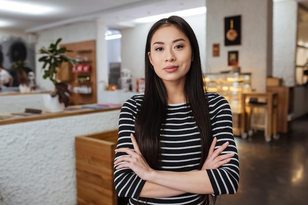 Mujer asiática con los brazos cruzados en la cafetería