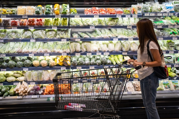 Mujer asiática en busca de vegetales orgánicos en el estante del supermercado.
