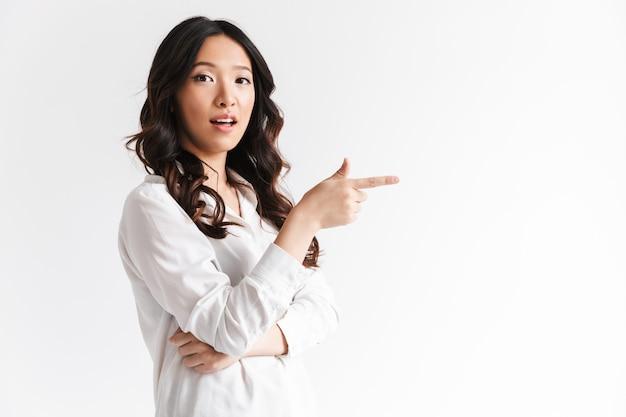 Mujer asiática con cabello largo y oscuro con hermosa sonrisa y señalar con el dedo a un lado