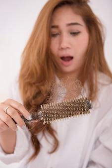 Mujer asiática cabello largo con un peine y cabello problemático sobre fondo blanco.