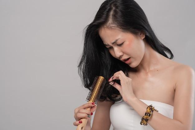 Mujer asiática cabello largo con un peine y cabello problemático sobre fondo gris