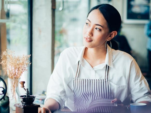 Mujer asiática con café en café