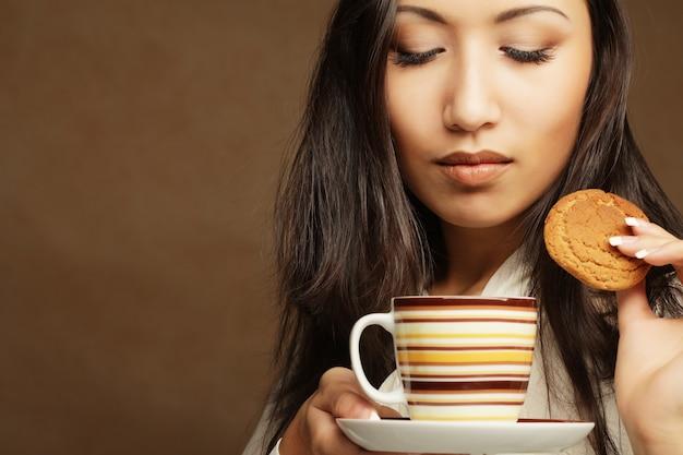 Mujer asiática con café y galletas.
